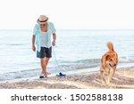 A Man With The Dog On The Beach.