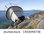 Small photo of Close up photo of recreational boat after collision with rocks. Vacation trip gone awry. Photographed at Norwegian coast, Scandinavia.