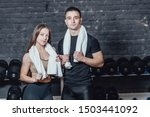 Small photo of Young sporty couple guy and girl standing in gym. During this, the white scumbag is held on the neck.