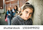 Small photo of A sad girl intimidation moment on the elementary Age Bullying in Schoolyard