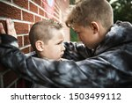 Small photo of sad intimidation moment Elementary Age Bullying in Schoolyard