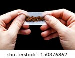Hands Rolling A Cigarette Pape...