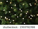 Fir tree branches with glowing yellow Christmas light as background