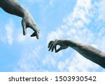 Small photo of two hands, fragment of old statue. hands reaching each other with fingers against sky background. touch, contact, art minimal symbol. Creation of Adam metaphor by Michelangelo