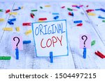 Small photo of Conceptual hand writing showing Original Copy. Business photo showcasing Main Script Unprinted Branded Patented Master List Crumbling sheet with paper clips placed on the wooden table.