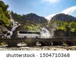 Tourist bus traveling on the road Latefossen Waterfall Odda Norway. Latefoss is a powerful, twin waterfall.