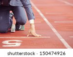 Small photo of A businessman on a track ready to run