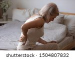 Upset mature woman suffering from backache after sleep, rubbing stiff muscles, unhappy older female sitting on bed at home, feeling discomfort, because of bad posture or uncomfortable bed