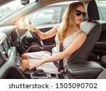 Small photo of girl car, right-hand drive, left-hand traffic, reversing, parking lot near shopping center. Engaging reverse gear, looking at rear window, checking back row passengers, driving safety at mall.
