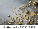 Small photo of Holiday background with golden Christmas decorations and New year 2020 numbers and confetti top view.