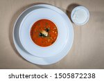 Stock photo upper view on white bowl on big saucer with solaynka soup decorated with piece of salted herring 1505872238