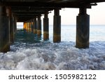 Small photo of the riotous lapping of the waves under the pier