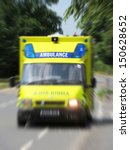Small photo of Ambulance in road with zoom effect focusing on sign.