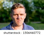 Small photo of Enraged infuriated man. Portrait of a young man on nature background. Emotion facial expression.