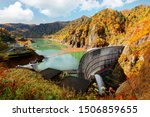 Autumn scenery of vibrant fall colors on the rocky cliffs surrounding Hoheikyo Dam in a beautiful gorge under environmental protection in Shikotsu-Toya National Park, in Sapporo, Hokkaido, Japan