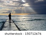 a man on a jetty silhouetted... | Shutterstock . vector #150712676