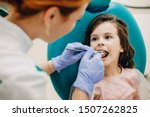 Sweet child doing a teeth examination by a professional specialist in a pediatric stomatology.