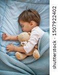 Small photo of Adorable redhead toddler baby sleeping with plush toy in sofa. Morning slumber. Baby toddler asleep with teddy bear. Little sweet toddler boy sleeping in his bed