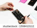 Small photo of KYIV, UKRAINE - FEBRUARY 27 2019: Smart Phone Battery Change Repair Maintenance. Repairman Hand Fix Smartphone Back Part Disassemble with Tweezers. Mobile Cellphone Assembly. Technician Work
