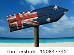 Small photo of Australia flag wooden sign with a beach on background - Oceania