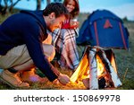 young man kindling firewood in... | Shutterstock . vector #150869978