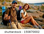Handsome hiker looking at camera with his girlfriend on background - stock photo
