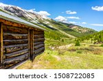 Independence Pass mining townsite wooden cabin in White River National Forest in Colorado with green pine trees and snow mountain peaks