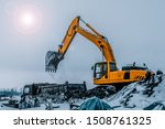 Small photo of Excavator is loading excavation to the truck. Excavators are heavy construction equipment consisting of a boom, dipper or stick , bucket and cab on a rotating platform