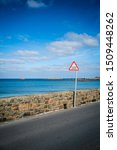 Small photo of Filter in turn sign at the beautiful sun drenched Cobo Bay on the west coast of the island of Guernsey in the Channel Islands, UK. Filter in turn is a famous Guernsey alternative to Give Way.