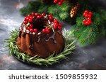 Small photo of Christmas chocolate bundt cake with glaze decorated with fresh berries and rosemary. Winter baking at Xmas or New Year with decorations on dark background