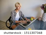 Small photo of Indoor photo of pretty concentrated female with short blond hair, wearing casual clothes, sitting next to laptop in headphones and wring text