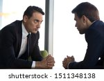 Small photo of Confident businessmen with clasped hands sitting opposite, debate concept, business partners negotiations, difficult interview, negotiators conflict, confrontation, struggle for leadership at work