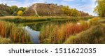 Small photo of Small scenic lake with shores overgrown with reed mace at the foot of the hill in autumn day, panoramic view