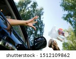 Small photo of a female hand throws a handful of garbage accumulated in the car through the open window of the car - coffee glasses, bags, crumpled paper. Flying objects are slightly blurred to enhance the effect of