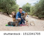 Stock photo professional dog walker or pet sitter with a pack of cute different breed and rescue dogs enjoying 1512341705