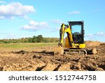 Small photo of Mini excavator digging earth in a field or forest. Laying underground sewer pipes during the construction of a house. Digging trenches for a gas pipeline or oil pipeline. Earthwork, foundation pit