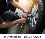 Small photo of Removing car mechanic to repair the leaky tire car wheels.Mechanic changing a car tire on a vehicle a hoist using an electric drill to loosen the bolts .concept of service or replacement.