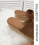 Stock photo brown female espadrilles close up on a platform on a background of white fur 1512877532