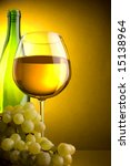 a glass bottle of white wine and green grape - stock photo
