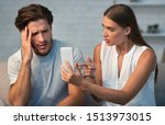 Small photo of Infidelity Concept. Wife Showing Her Cheating Husband His Cellphone Demanding Explanation Sitting On Couch At Home.
