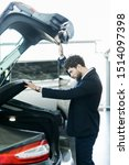 Small photo of It is so roomy inside. Handsome young car salesman showing the car trunk to the customer