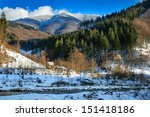 coniferous forest on the snowy mountain peaks near the river in winter day - stock photo