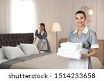Chambermaid With Stack Of Fres...