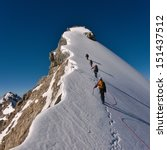 Stock photo tied climbers climbing mountain with snow field tied with a rope with ice axes and helmets 151437512