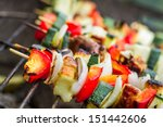 Skewers with chiken and vegetables on the grill - stock photo
