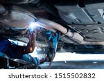 The hand of a mechanic or welder is fixing a car exhaust system by welding the exhaust pipe. Sparks of automobile exhaust pipe welding. Auto services. Selective focus. Copy space. - stock photo