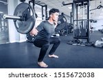 Asian young atheletic man in sportswear doing squat at gym