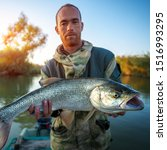 Small photo of Young angler holds Asp fish (Aspius aspius) being on the river in Astrakhan Region, Russia