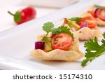 Corn tortilla chips fill with fresh cherry tomatoes salsa. - stock photo