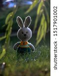 Stock photo handmade knitted toy hare amigurumi rabbit on the nature background funny hare in green pants 1517901002